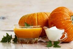 家在白色木桌做了南瓜奶油色汤用南瓜和荷兰芹叶子 南瓜奶油色汤 免版税库存照片