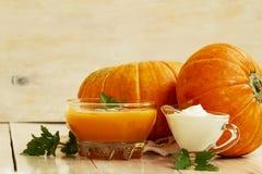 家在白色木桌做了南瓜奶油色汤用南瓜和荷兰芹叶子 南瓜奶油色汤 库存照片