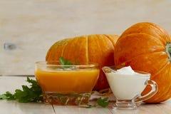 家在白色木桌做了南瓜奶油色汤用南瓜和荷兰芹叶子 南瓜奶油色汤 免版税库存图片
