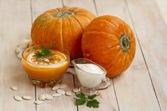 家在白色木桌做了南瓜奶油色汤用南瓜和荷兰芹叶子 南瓜奶油色汤 图库摄影