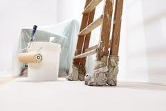 画家墙壁概念,梯子,桶,卷油漆 免版税库存照片