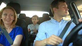 家庭、妈妈爸爸和儿子骑马在汽车,他们唱歌曲与全家 股票视频