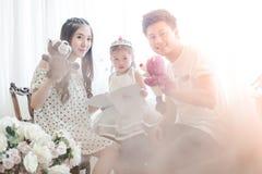家庭、孩子和家庭概念-微笑的父母和小女孩 库存图片