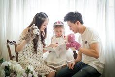 家庭、孩子和家庭概念-微笑的父母和小女孩 免版税库存图片
