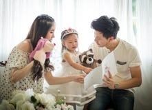 家庭、孩子和家庭概念-微笑的父母和小女孩 图库摄影
