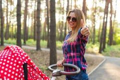 家庭、孩子和父母身分概念-有婴儿推车的愉快的母亲在公园 免版税库存图片