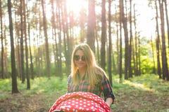 家庭、孩子和父母身分概念-走和推挤一辆婴儿推车的年轻母亲在有新出生的公园 美丽 库存图片