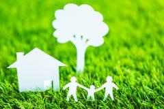 家庭、房子和树纸裁减在绿草 库存图片