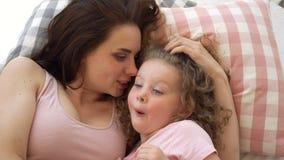 家庭、母亲和女儿在床上说谎并且谈话 股票录像