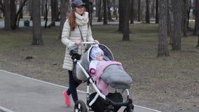 家庭、母性和人概念-有睡觉在婴儿推车的女婴的愉快的母亲走在春天公园 股票视频