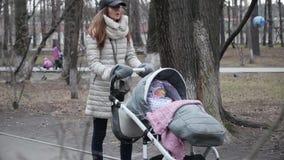 家庭、母性和人概念-有睡觉在婴儿推车的女婴的愉快的母亲走在春天公园 股票录像