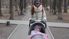 家庭、母性和人概念-有睡觉在婴儿推车的女婴的母亲走在春天公园 股票录像