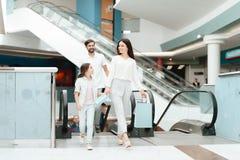 家庭、父亲、母亲和女儿在自动扶梯上升在购物中心 免版税库存图片