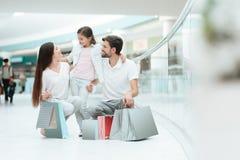 家庭、父亲、母亲和女儿在购物中心坐 库存图片
