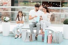 家庭、父亲、母亲和女儿坐长凳在购物中心 女孩是恼怒和哀伤的 免版税库存照片
