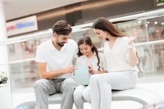 家庭、父亲、母亲和女儿坐长凳在购物中心 女孩看在一个袋子里面 免版税库存照片