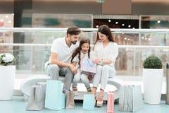 家庭、父亲、母亲和女儿坐长凳在购物中心 女孩看在一个袋子里面 库存图片