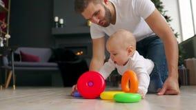 家庭、父权和人概念-有在家使用与玩具的一点小儿子的愉快的父亲 影视素材