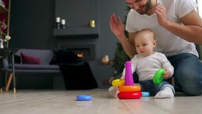 家庭、父权和人概念-有在家使用与玩具的一点小儿子的愉快的父亲 股票录像