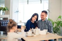 家庭、父母身分、技术人概念-接近愉快的母亲的父亲和吃的小女孩晚餐,孩子 图库摄影