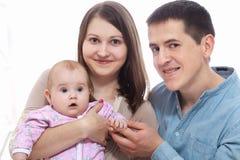 家庭、父母身分和人概念-愉快的母亲,有小女儿的父亲在家 免版税库存图片