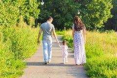 家庭、父母身分和人概念-愉快的走在夏天的母亲、父亲和小女孩停放 免版税库存图片