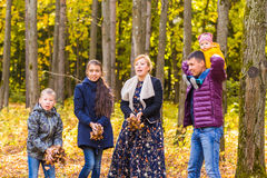 家庭、秋天、幸福和人概念-母亲、使用在秋天的父亲、儿子和女儿停放 库存图片