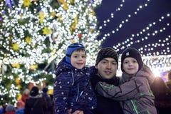 家庭、童年、季节和人概念-愉快在冬天穿衣在多雪的城市背景 免版税库存图片