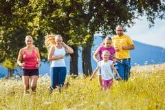家庭、跑为体育的母亲、父亲和孩子 免版税库存图片