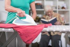 家庭一个老妇人的帮手电烙的衣裳 免版税库存照片