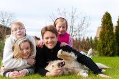 家庭一起与狗坐草甸 免版税库存图片