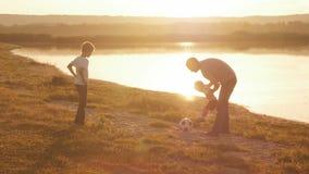年轻家庭一起嬉戏踢在海滩的橄榄球橄榄球在日落 股票视频