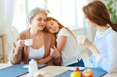 家庭三世代在家拥抱在厨房里的祖母、母亲和孩子 免版税图库摄影