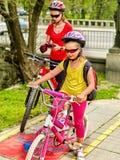 家庭与循环在自行车车道的背包的自行车乘驾 免版税库存照片