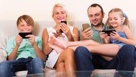 家庭与智能手机一起使用 库存图片
