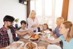 家庭为感恩的一顿欢乐晚餐聚集了 大家在板材投入食物 图库摄影