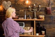 家庭书库概念 寻找书的女孩在猎场看手人房子里  偶然成套装备的女孩在木葡萄酒内部 免版税图库摄影