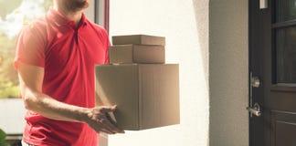 家庭交付服务-有箱子的送货员 免版税库存照片
