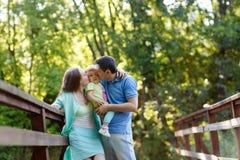 家庭亲吻他们的女儿的妈妈和爸爸画象户外  免版税图库摄影