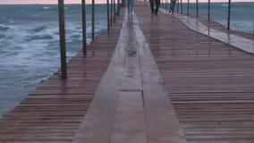 家庭从波浪跑在风暴的海码头 波浪通过木码头飞溅在海 美丽 影视素材