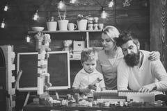 家庭休闲概念 演奏玩具的孩子 父母拥抱,观看儿子使用,享受父母身分 与父母的孩子 免版税库存图片