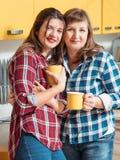 家庭休闲母亲女儿茶杯手 免版税图库摄影