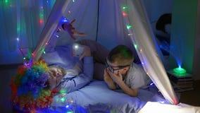 家庭休闲,有爸爸的快乐的孩子小丑假发的和讲在帐篷的可怕的故事 股票视频