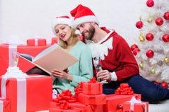 家庭传统 家庭拥抱在圣诞树附近的饮料香槟,当看全家福象册时 记住明亮 免版税图库摄影