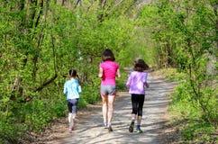 家庭体育、愉快的活跃跑步母亲和的孩子户外 图库摄影