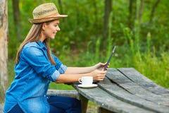 家庭作业在有膝上型计算机和咖啡杯的庭院里 免版税库存照片
