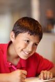 家庭作业的年轻男孩图画 库存照片