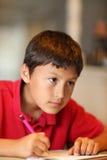 家庭作业的年轻男孩图画 图库摄影