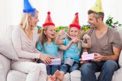 家庭佩带的党帽子和庆祝孪生生日 免版税库存图片