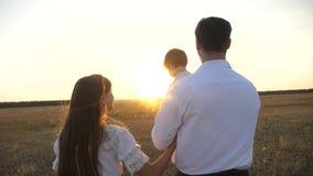 家庭使用与婴孩在日落 与她的女儿的爸爸和妈妈步行她的在日落的胳膊的 ?? 股票录像